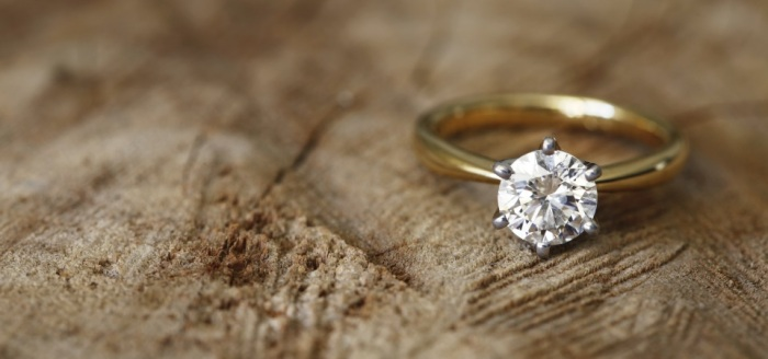 Solitaire engagement diamond ring won wooden organic background.